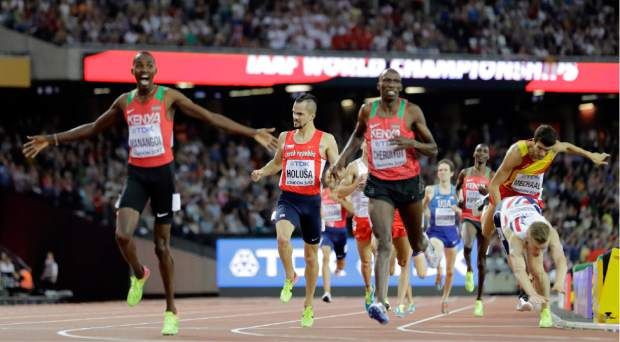 Kenya's Elijah Motonei Manangoi, left, celebrates winning the gold medal in the Men's 1500m final as bronze medalist Norway's Filip Ingebrigtsen, right, falls during the World Athletics Championships in London Sunday, Aug. 13, 2017. (AP Photo/David J. Phillip)