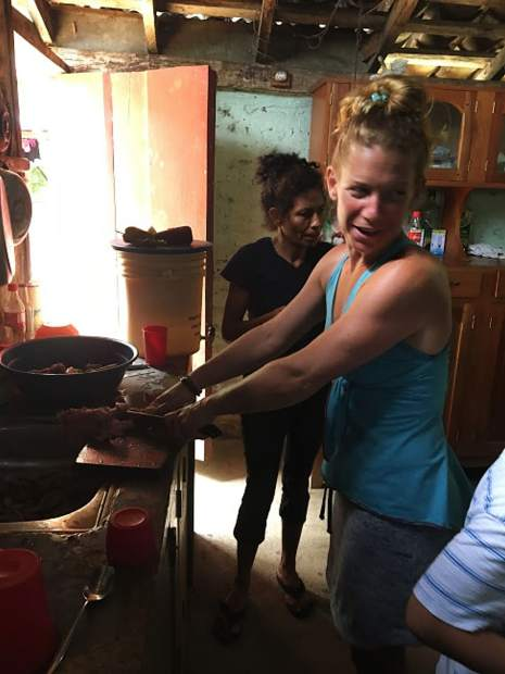 Andrea Chacos helps clean up in a kitchen in El Tambo, Nicaragua, after a chicken beheading to make soup.