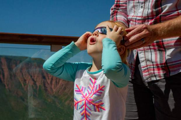 Four-year-old Evelyn Botkin looks in amazement at the Great American Eclipse through her special eclipse glasses at the Glenwood Caverns Adventure Park Monday morning.