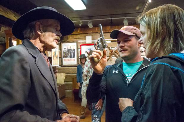R.W. Doc Boyle shows Christine and Ryan Petchenick a few of his favorite guns during the grand opening of the Doc Holliday Museum on Friday evening.