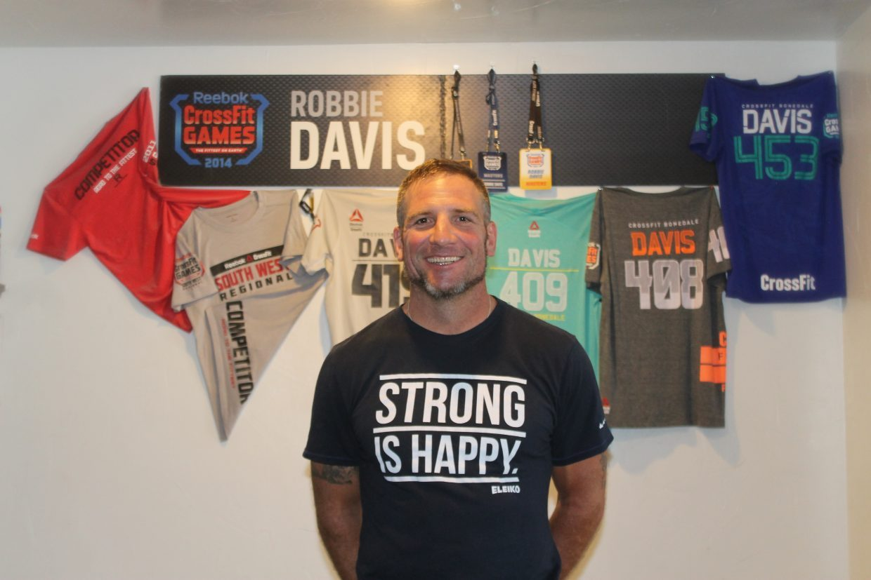 Robbie Davis stands in front of shirts and banners from the CrossFit Games.