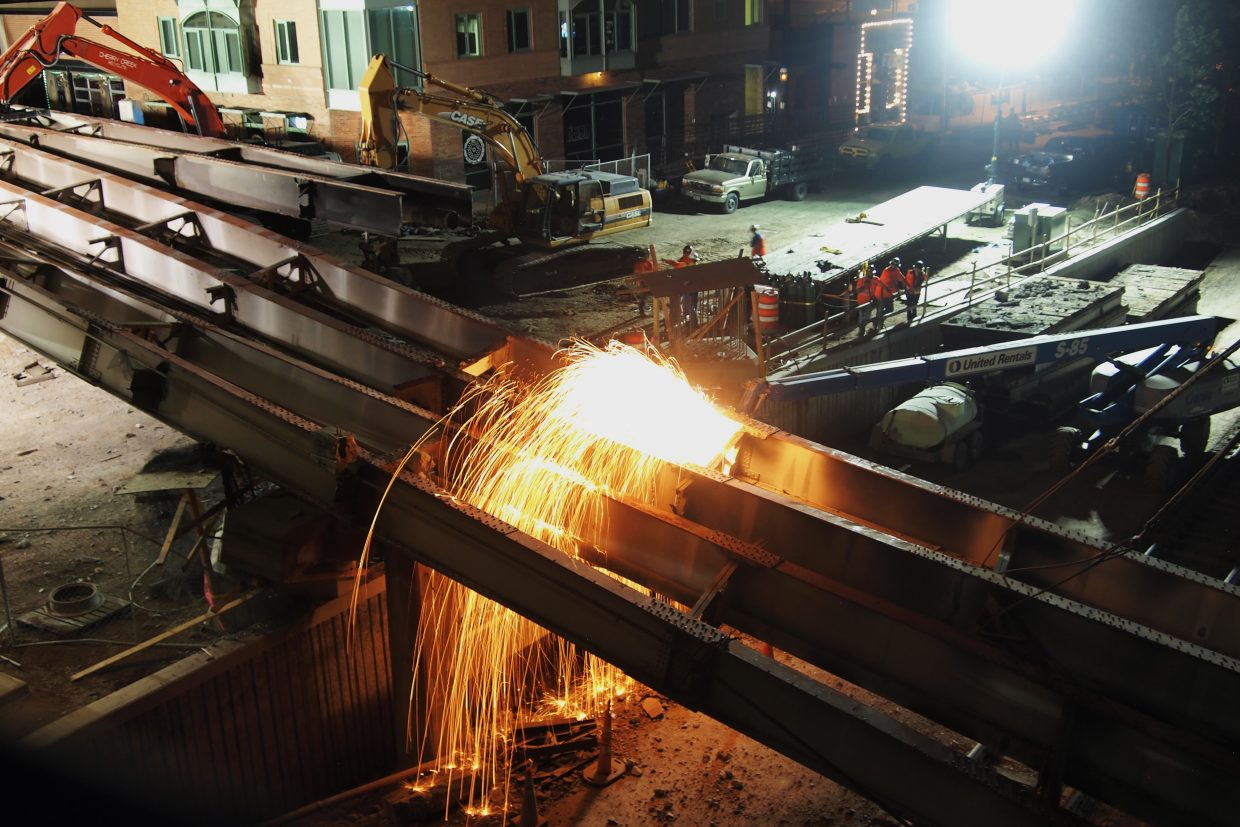 Crews work at cutting apart collapsed bridge girders that fell Tuesday evening from the old Grand Avenue bridge.