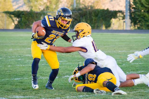 Rifle senior Brandon Fletchall eludes the tackle of Basalt's Raul Torres as Rifle senior Ramon Salvidrez attempts to block Torres on the play.