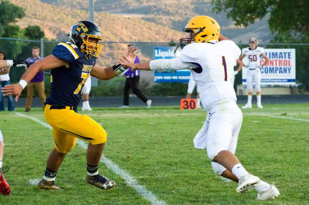 Rifle senior defensive lineman Connor Gould closes in on Basalt senior quarterback Trevor Reuss during Friday's Week 0 matchup at Bears Stadium.