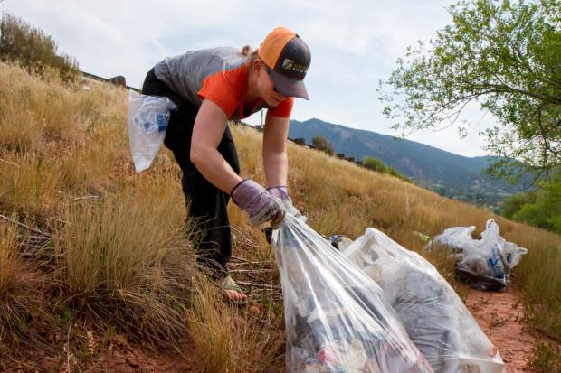 Katy-Joy Knapp brings piles of trash down from the hillside near the Glenwood Whitewater Park.