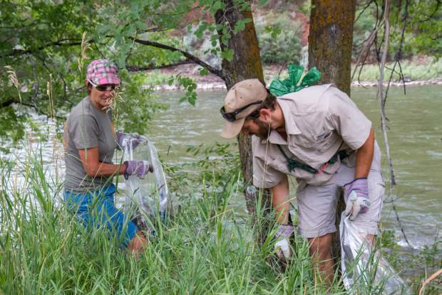 Volunteers Laurie Rink and Nate Higginson work together to pick up trash on river clean-up day on Saturday morning.