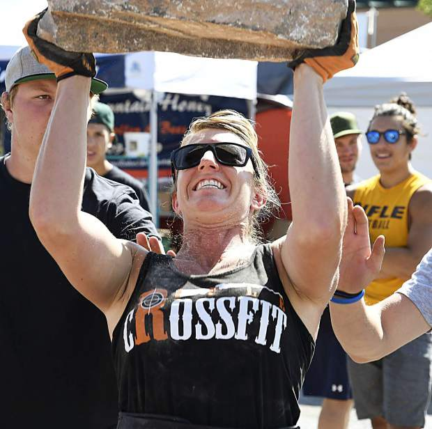 Karna Potter of RIfle hoists a 100-pound stone over her head in the overhead lift event in the Strongman competition Sunday at the Garfield County Fair in Rifle.