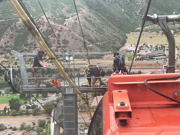A crew of three climbed up a pole to work on the Iron Mountain Tramway during a July 28 stoppage. Winds of about 40 mph blew the cable from its correct position, and so sensors automatically stopped the tram.