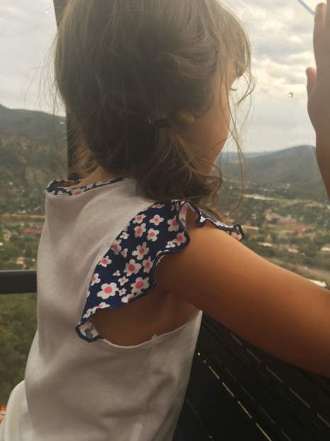 Isabella peers out the window of her tram cabin, watching as rescue workers walk below.