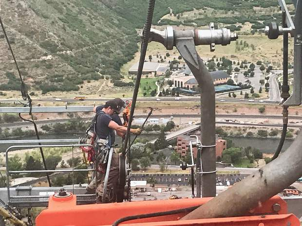 A worker uses a pry bar to move a cable back into position on Iron Mountain Tramway.