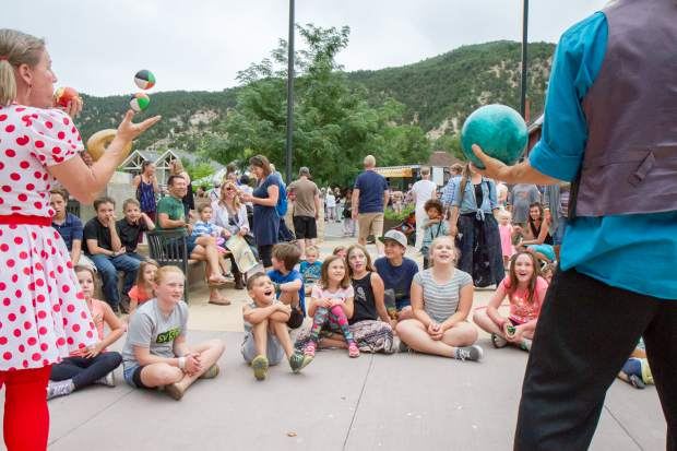 A group of kids and parents laugh and enjoy the show put on by the Salida Circus performers at the summer block party in downtown Glenwood Saturday evening.