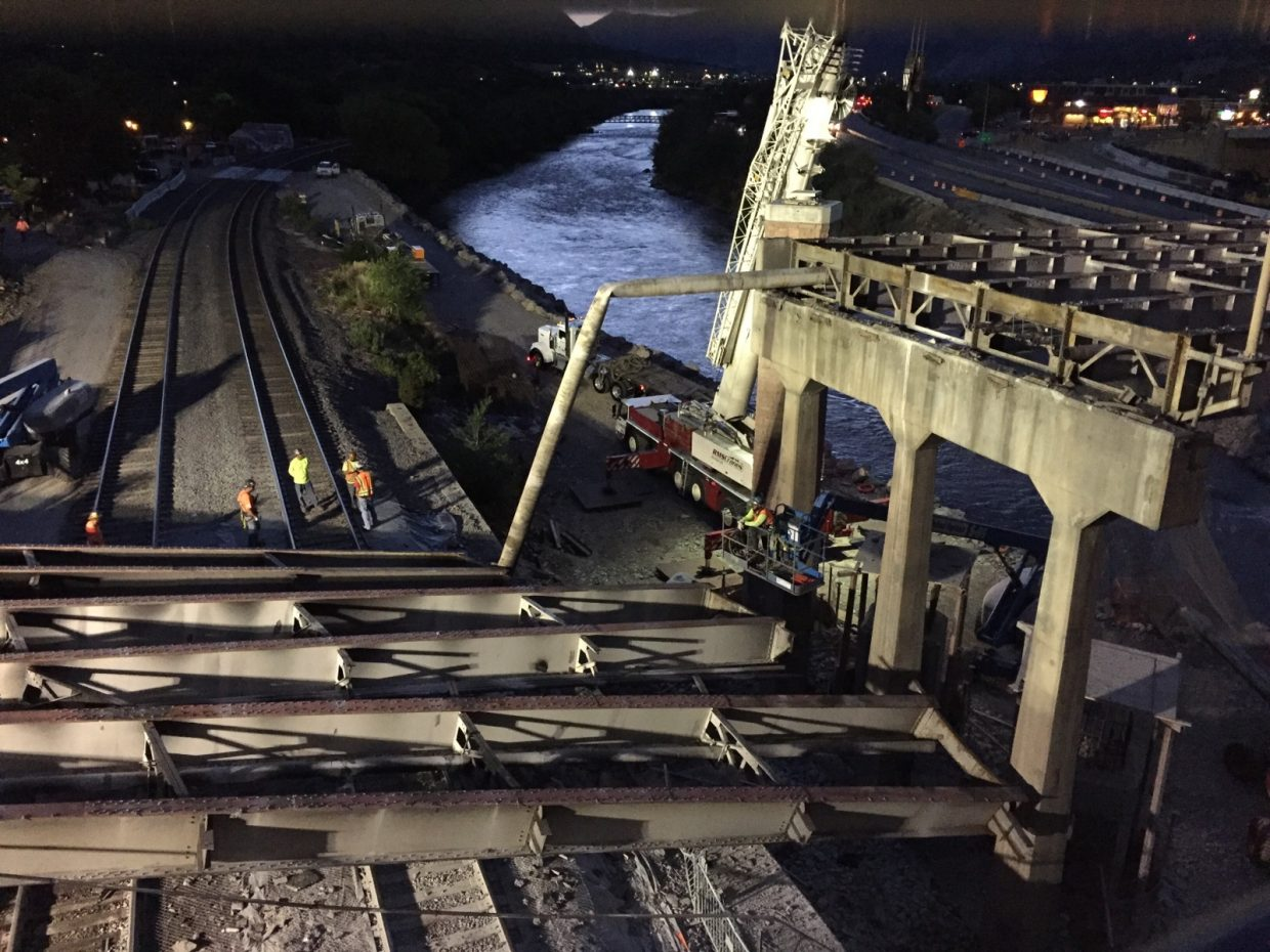 Steel beams from the old Grand Avenue bridge lie across Union Pacific Railroad tracks Tuesday evening after an accidental collapse.