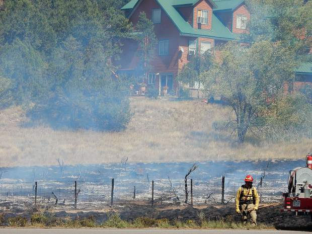 Basalt firefighters relax after knocking down the grass fire Friday. The flames came relatively close to homes in Aspen Junction.
