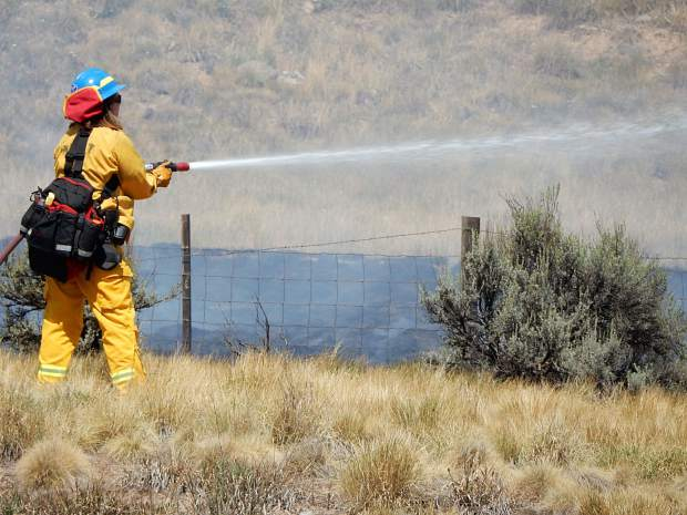 A Basalt firefighter sprays the east end of the grass land fire.