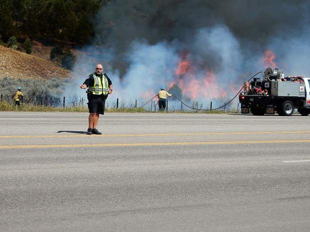 Basalt Police Chief Greg Knott directs traffic on Highway 82 while firefighters scramble to get the grass fire under control.