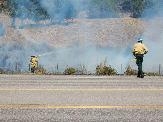 A Basalt firefighter sprays the grass fire.