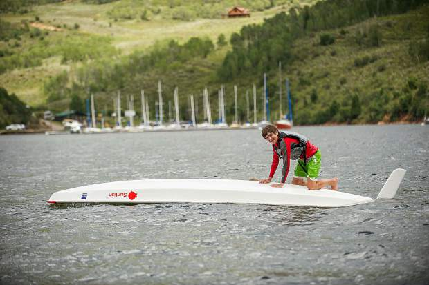 Spencer Perley, 14, swims back to his sunfish sailboat with the centerboard after purposefully capsizing on Tuesday on Ruedi Reservoir.