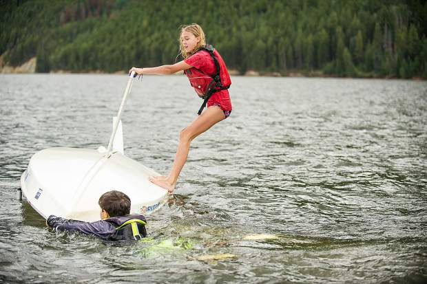 Hope White, 12, and Noah Incze, 10, work on practicing righting their sunfish sailboat after purposefully capsizing on Tuesday on Ruedi Reservoir.