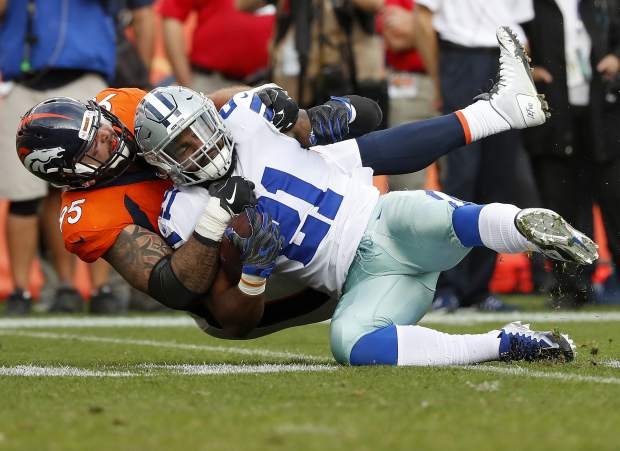 Dallas Cowboys running back Ezekiel Elliott (21) is tackled by Denver Broncos cornerback Chris Harris during the second half of an NFL football game, Sunday.