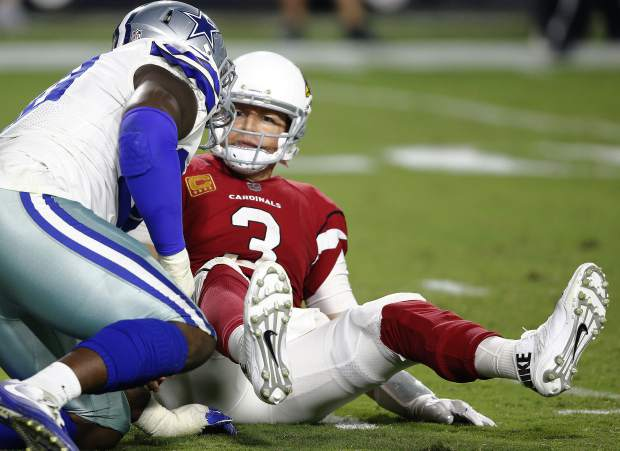 Arizona Cardinals quarterback Carson Palmer (3) looks at Dallas Cowboys defensive end Demarcus Lawrence after being sacked during the second half of an NFL football game, Monday, Sept. 25, 2017, in Glendale, Ariz. (AP Photo/Ross D. Franklin)