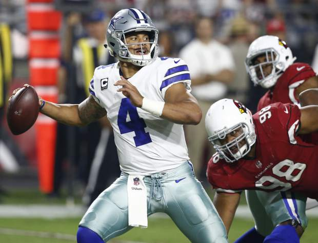Dallas Cowboys quarterback Dak Prescott (4) throws as Arizona Cardinals nose tackle Corey Peters (98) pursues during the second half of an NFL football game, Monday, Sept. 25, 2017, in Glendale, Ariz. (AP Photo/Ross D. Franklin)
