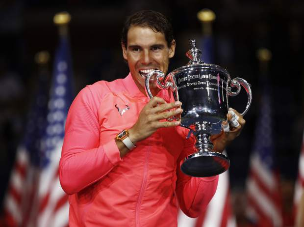 Rafael Nadal, of Spain, holds up the championship trophy after beating Kevin Anderson, of South Africa, in the men's singles final of the U.S. Open tennis tournament, Sunday, Sept. 10, 2017, in New York. (AP Photo/Julio Cortez)