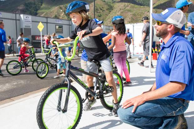 Second grader Keaton Olson gets some help from an Umbrella Roofing employee before trying out his brand new bike.