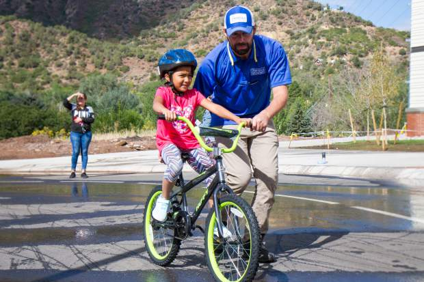 GSES second grader Dulce Dela Cruz tries out her brand new bike, with some assistance from Umbrella Roofing employee Steve Klehfoth, outside the school Friday morning.