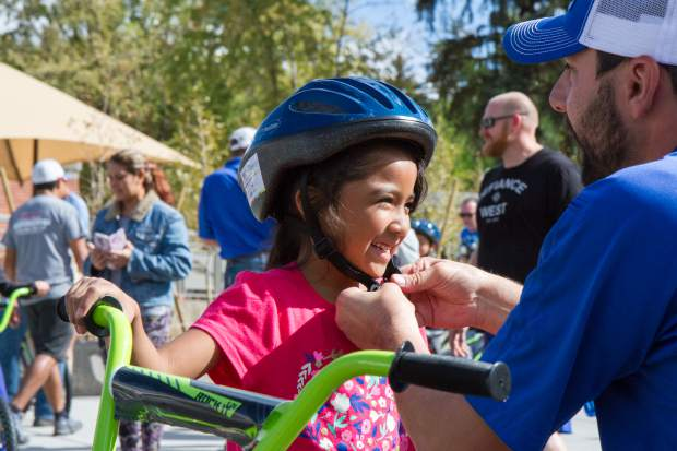 Second grader Dulce Dela Cruz gets fitted for her brand new helmet and bike at GSES Friday morning.