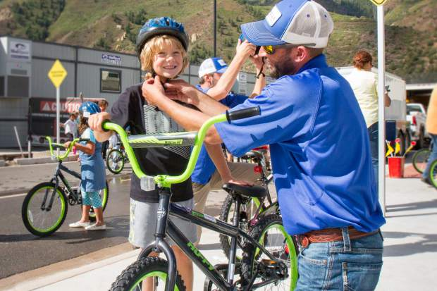 Second grader Keaton Olson gets some help from Umbrella Roofing employee Deric Barton before trying out his brand new bike.