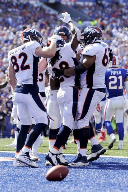 Denver Broncos players celebrate a touchdown run by running back Jamaal Charles (28) against the Buffalo Bills during the first half of an NFL football game, Sunday, Sept. 24, 2017, in Orchard Park, N.Y. (AP Photo/Adrian Kraus)