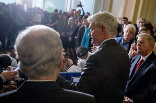 Sen. Bill Cassidy, R-La., flanked by Sen. Lindsey Graham, R-S.C., right, and Senate Majority Leader Mitch McConnell, R-Ky., left, speaks to reporters as they faced assured defeat on the Graham-Cassidy bill, the GOP's latest attempt to repeal the Obama health care law, at the Capitol in Washington, Tuesday, Sept. 26, 2017, in Washington. The decision marked the latest defeat on the issue for President Donald Trump and Senate Majority Leader Mitch McConnell in the Republican-controlled Congress. (AP Photo/Andrew Harnik)