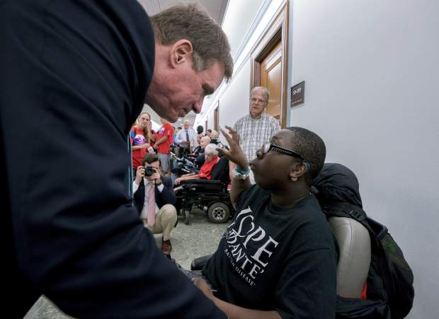 Sen. Mark Warner, D-Va., speaks with a person with disabilities outside a hearing room where the Senate Finance Committee will hold a hearing to consider the Graham-Cassidy healthcare proposal, on Capitol Hill, Monday, Sept. 25, 2017, in Washington. (AP Photo/Andrew Harnik)