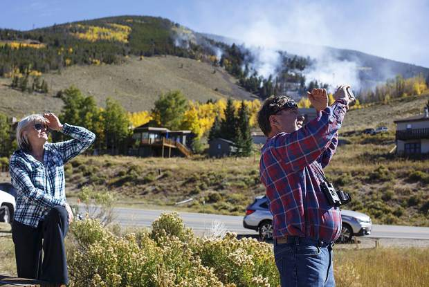 Silverthorne residents Marleen Goodman, left, and Dan Moroz take photos of helicopter action along Highway 6 of the Tenderfoot2 Fire Tuesday, Sept. 19, in Dillon.