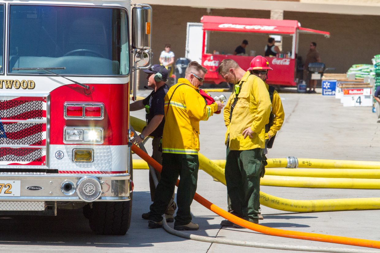 A group of firefighters prepare to battle a fire behind the Wal-Mart parking lot on Saturday afternoon.