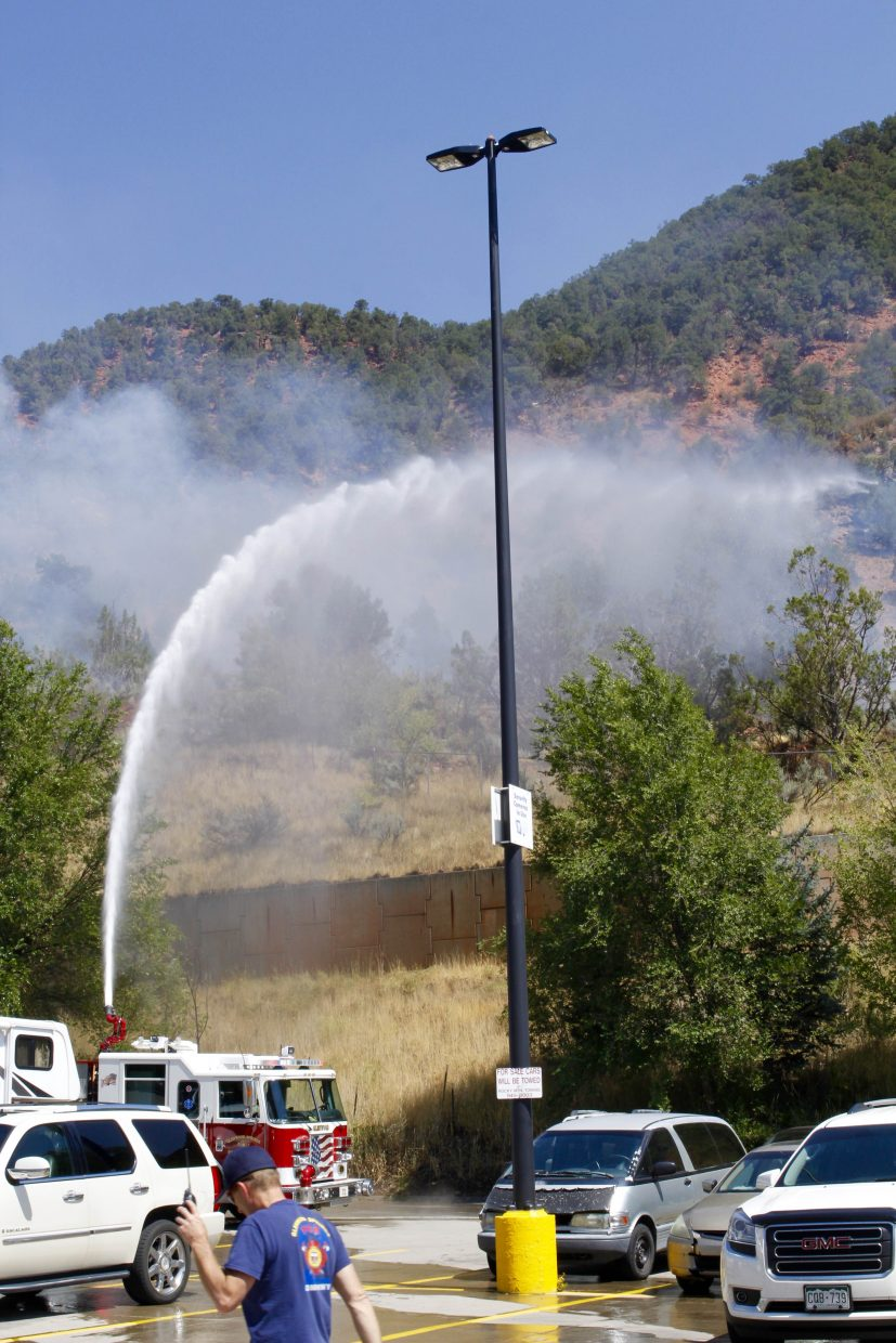 Crews work to fight a fire that started behind the Wal-Mart parking lot Saturday afternoon.
