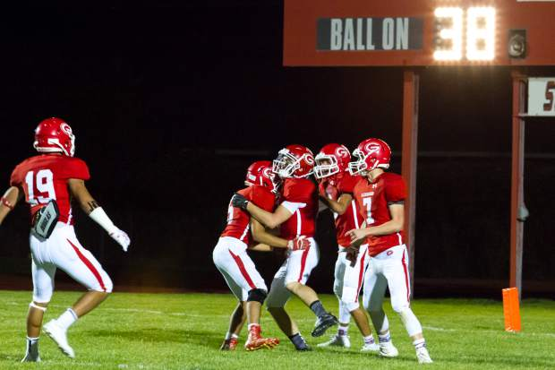 The Glenwood Springs Demons celebrate after a touchdown during Friday night's game against the Kennedy Commanders.