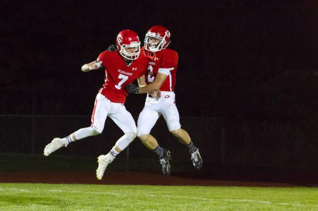 Glenwood Springs Demons Jack Richards (7) and John Jensen (2) celebrate after a touchdown during Friday night's game against the Kennedy Commanders.