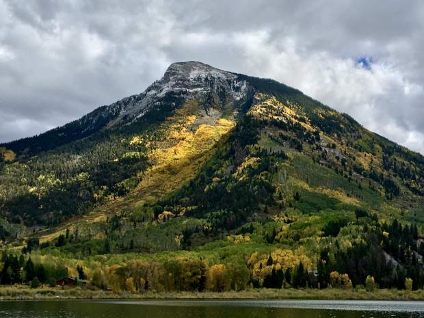 The sun peeks through the clouds hitting the golden yellow aspens on Whitehouse Mountain in front of Beaver Lake in Marble, Colorado.