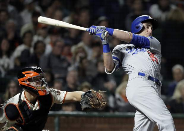 FILE - In this Sept. 13, 2017, file photo, Los Angeles Dodgers' Cody Bellinger follows through on a two-run home run against the San Francisco Giants during the fifth inning of a baseball game, in San Francisco. Nearly two decades after the height of the Steroids Era, Major League Baseball is on track to break its season record for home runs on Tuesday with nearly two weeks left in the season. There were 5,663 home runs hit through Sunday, 30 shy of the record 5,693 set in 2000. (AP Photo/Marcio Jose Sanchez, File)