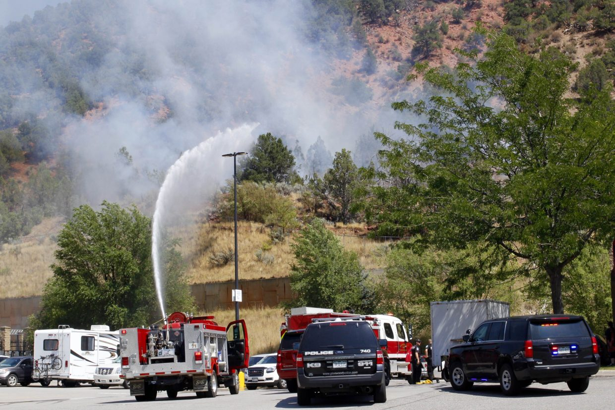 Firefighters shoot water from a firetruck onto the fire near Wal-Mart Saturday afternoon.