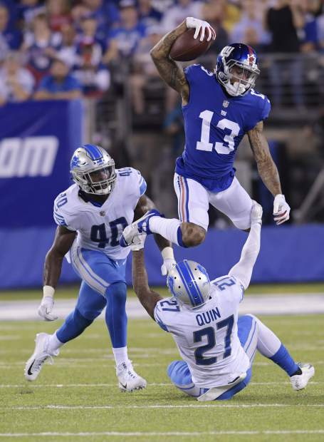 New York Giants wide receiver Odell Beckham (13) leaps over Detroit Lions' Glover Quin (27) as Jarrad Davis (40) watches during the first half of an NFL football game, Monday, Sept. 18, 2017, in East Rutherford, N.J. (AP Photo/Bill Kostroun)