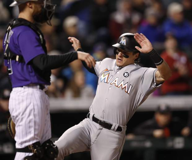 Miami Marlins' Derek Dietrich, right, slides safely into home plate to score on a double by Miguel Rojas as Colorado Rockies catcher Jonathan Lucroy stands near the plate during the fourth inning of a baseball game Monday, Sept. 25, 2017, in Denver. Miami won 5-4. (AP Photo/David Zalubowski)