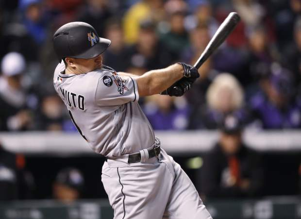 Miami Marlins' J.T. Realmuto follows through on an RBI single off Colorado Rockies starting pitcher Tyler Chatwood during the fourth inning of a baseball game Monday, Sept. 25, 2017, in Denver. Miami won 5-4. (AP Photo/David Zalubowski)