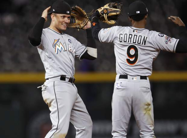 Miami Marlins shortstop Miguel Rojas, left, celebrates with second baseman Dee Gordon after Colorado Rockies' Charlie Blackmon hit into a double play to end a baseball game Monday, Sept. 25, 2017, in Denver. Miami won 5-4. (AP Photo/David Zalubowski)