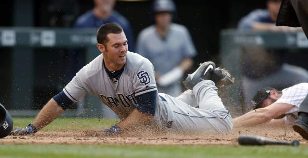 San Diego Padres' Matt Szczur, left, slides safely across home plate to score the go-ahead run as Colorado Rockies relief pitcher Greg Holland falls while trying to make the tag in the ninth inning of a baseball game Sunday, Sept. 17, 2017, in Denver. (AP Photo/David Zalubowski)