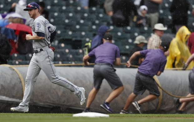 San Diego Padres left fielder Cory Spangenberg, front, runs for the dugout as members of the field crew pull the tarpaulin to cover the field as rain sweeps over Coors Field in the bottom of the fifth inning of a baseball game against the Colorado Rockies, Sunday, Sept. 17, 2017, in Denver. (AP Photo/David Zalubowski)