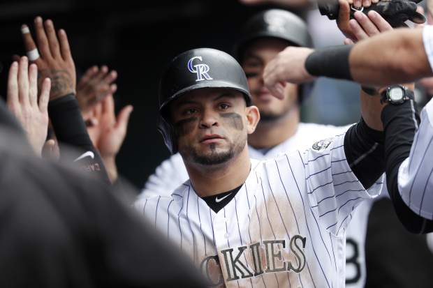 Colorado Rockies' Gerardo Parra is congratulated by teammates after he and Nolan Arenado, back, scored on a double hit by Trevor Story off San Diego Padres starting pitcher Jhoulys Chacin in the fourth inning of a baseball game Sunday, Sept. 17, 2017, in Denver. (AP Photo/David Zalubowski)