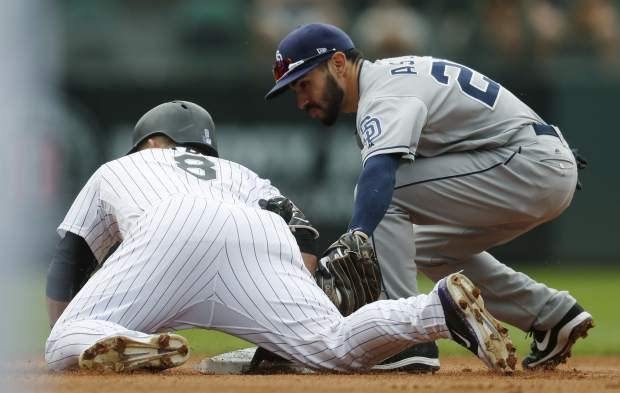 Colorado Rockies' Gerardo Parra, left, slides safely into second base with an RBI-double as San Diego Padres second baseman Carlos Asuaje fields the throw from the outfield in the fourth inning of a baseball game Sunday, Sept. 17, 2017, in Denver. (AP Photo/David Zalubowski)