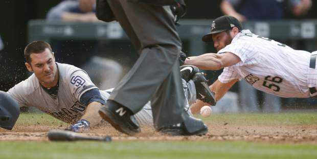 San Diego Padres' Matt Szczur, left, slides safely across home plate to score the go-ahead run as Colorado Rockies relief pitcher Greg Holland, right, drops the throw for an error following a sacrifice bunt by the Padres' Austin Hedges in the ninth inning of a baseball game Sunday, Sept. 17, 2017, in Denver. (AP Photo/David Zalubowski)